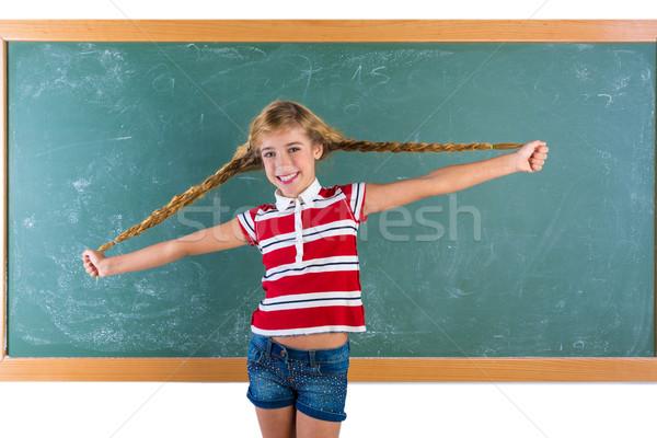 Braided student blond girl playing with braids Stock photo © lunamarina