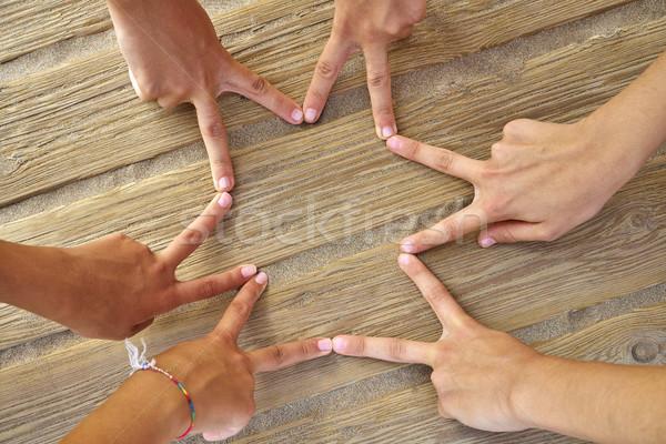 Star shape with six hand fingers on a beach Stock photo © lunamarina