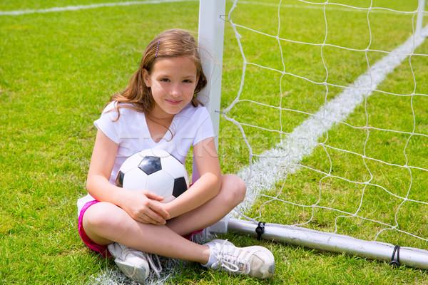 Soccer football kid girl relaxed on grass with ball Stock photo © lunamarina