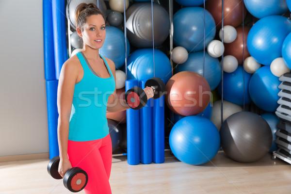 Blue eyes girl at gym weightlifting dumbbells Stock photo © lunamarina