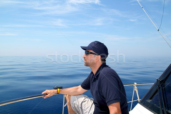 Sailor man sailing boat blue calm ocean water Stock photo © lunamarina