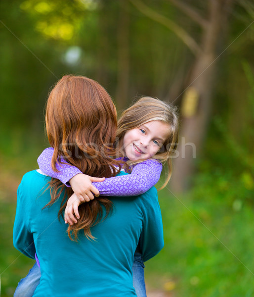 Mum holding daughter kid girl in her arms rear view smiling Stock photo © lunamarina