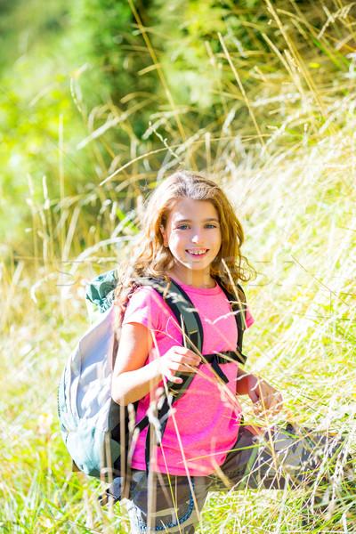Explorer kid girl walking with backpack in grass Stock photo © lunamarina