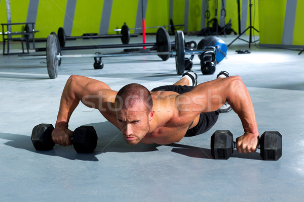 Gym man push-up strength pushup exercise with dumbbell Stock photo © lunamarina