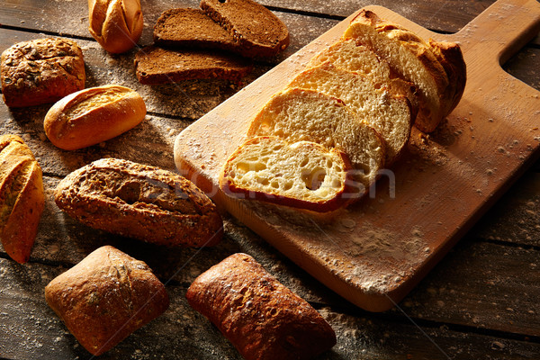 Stock photo: Bread varied loafs sliced on wood board in rustic