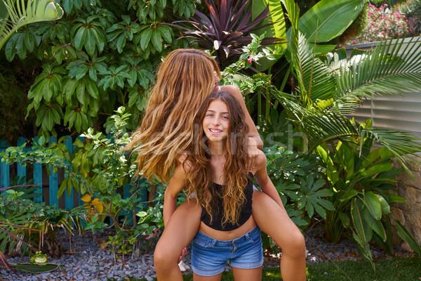 Best friends teen girls piggyback on backyard Stock photo © lunamarina