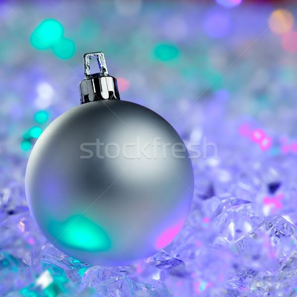 christmas silver bauble on colorful glowing ice Stock photo © lunamarina