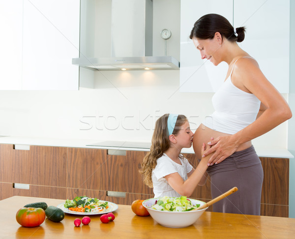 Stock photo: Beautiful pregnant mother with her daughter at kitchen