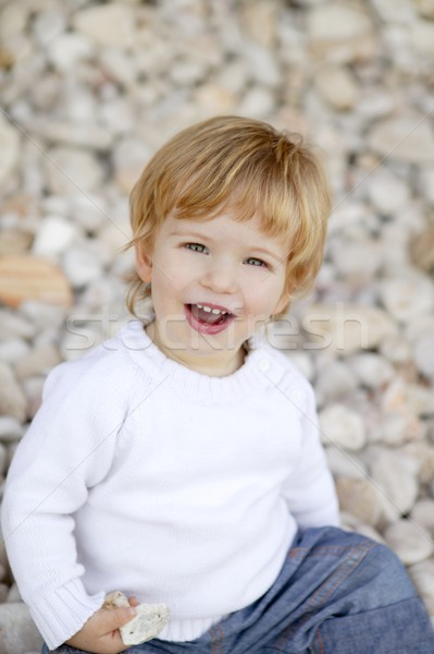 Blond boy smiling on a rolling stones background Stock photo © lunamarina