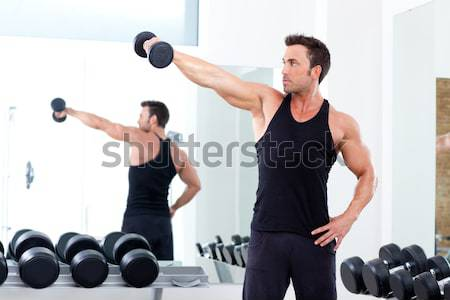Stock photo:  woman with weight training equipment on sport gym