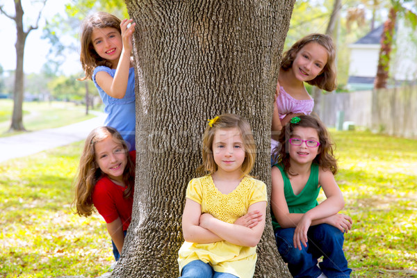 Children group of sisters girls and friends on tree trunk Stock photo © lunamarina