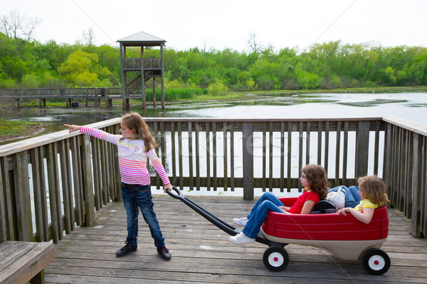 girls looking at park lake with outdoor dump cart Stock photo © lunamarina