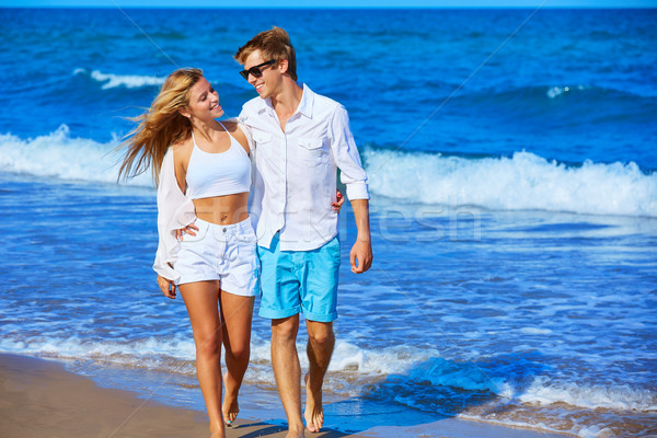 Blond young couple walking in the beach shore Stock photo © lunamarina
