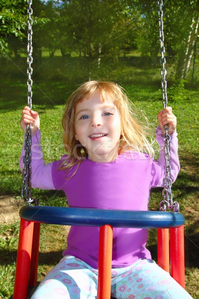 girl swinging on swing happy in meadow grass park Stock photo © lunamarina