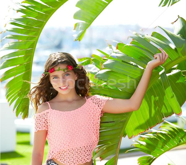 Brunette kid girl at banana tree leaves in bright day Stock photo © lunamarina