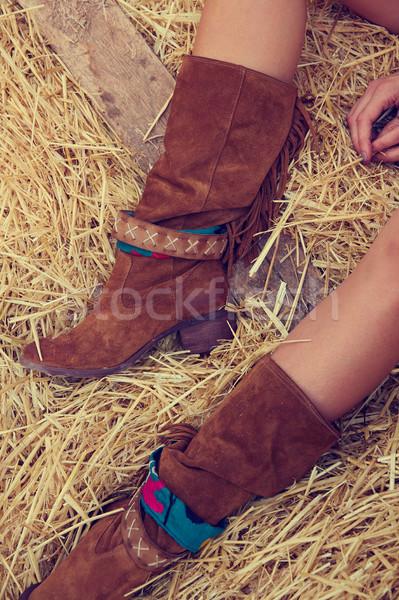 female legs with leather brown on straw bale Stock photo © lunamarina