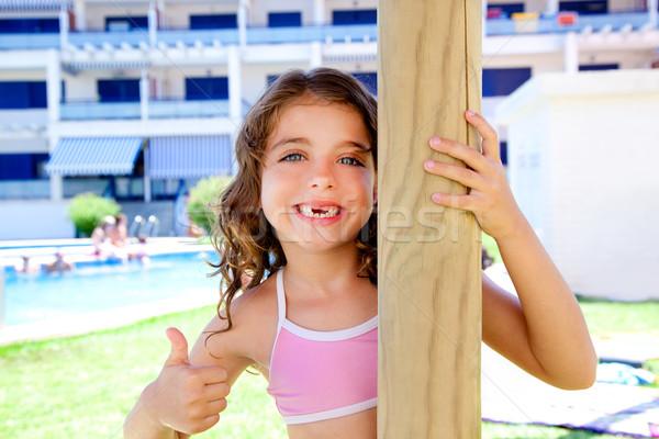 indented kid girl ok gesture in pool garden Stock photo © lunamarina