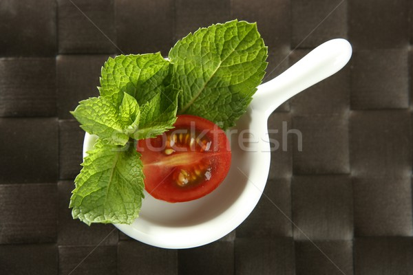Half cherry tomato in a little dish with basil Stock photo © lunamarina
