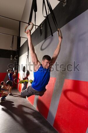 Muscle ups rings woman swing workout at gym Stock photo © lunamarina