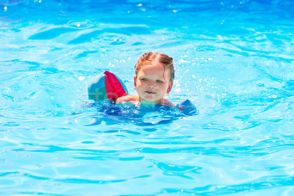 Baby girl swimming in pool with floats sleeves Stock photo © lunamarina