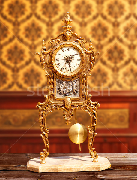Ancient vintage brass pendulum clock in classic indoor Stock photo © lunamarina