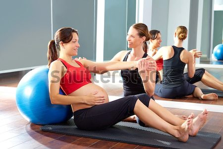 Pilates women group lying on mat with gym instructor Stock photo © lunamarina