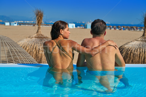 Tourist couple in infinity pool rear view Stock photo © lunamarina