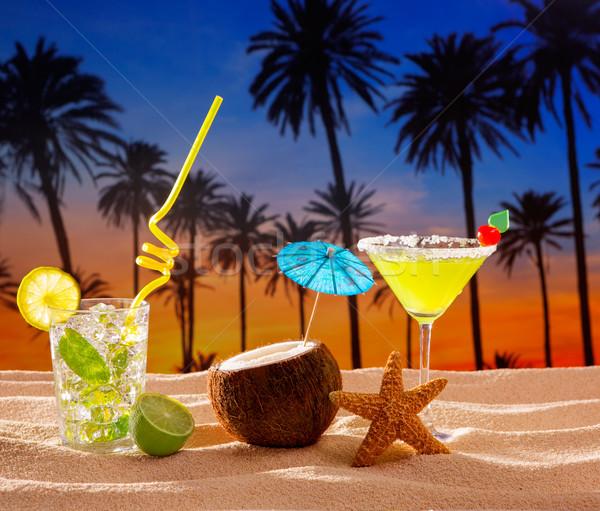 Praia coquetel pôr do sol palmeira areia mojito Foto stock © lunamarina