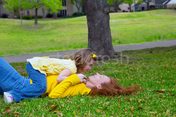 Daughter and mother playing lying on park lawn Stock photo © lunamarina
