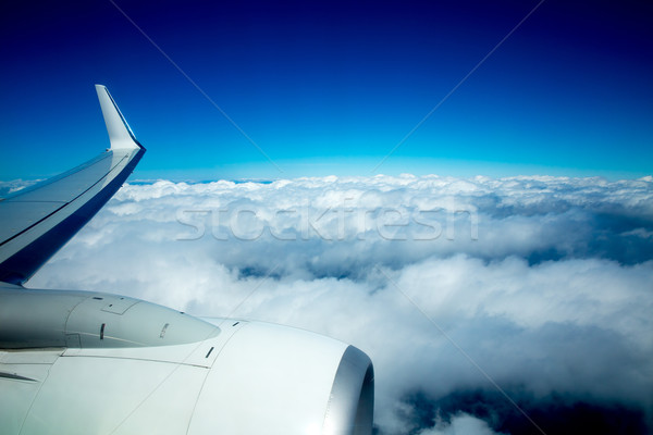 Airplane wing flying over fluffy clouds in blue sky Stock photo © lunamarina