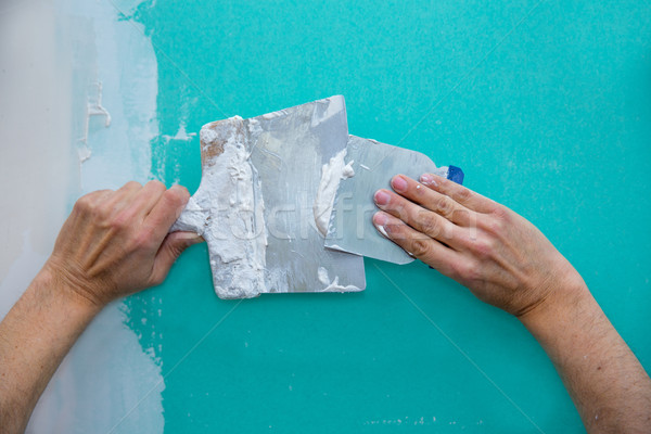 Plastering man hands with plaste on drywall plasterboard Stock photo © lunamarina