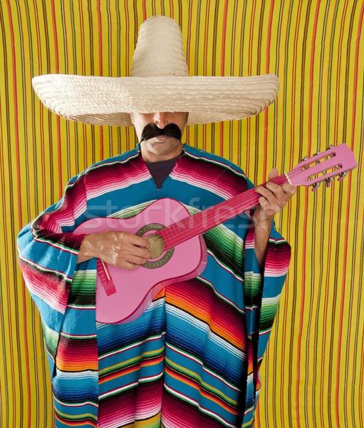 Mexican man serape poncho sombrero playing guitar Stock photo © lunamarina