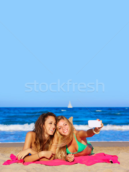 happy girl friends selfie portrait lying on beach Stock photo © lunamarina