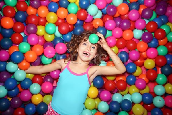 little girl playing lying in colorful balls park playground Stock photo © lunamarina