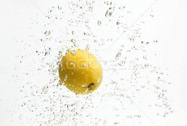 Stock photo: One yellow lemon and water.