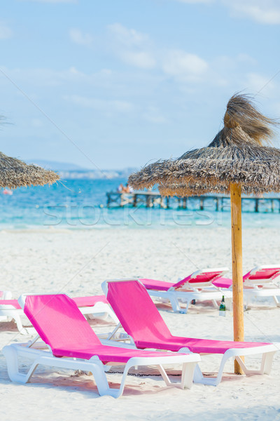 Two chairs and umbrella on the beach. Stock photo © macsim