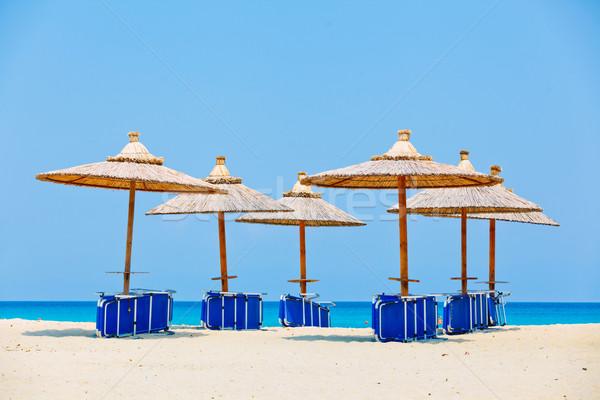 Parasols strand zonsondergang zomer Blauw zand Stockfoto © macsim