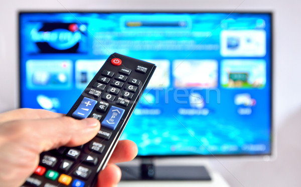 Smart tv and hand pressing remote control Stock photo © mady70