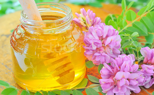 glass jar full of honey and stick with acacia pink and white flo Stock photo © mady70