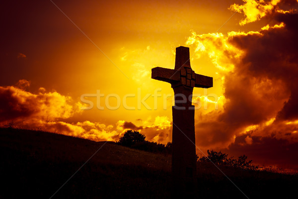 a stone cross in front of a dramatic evening sky Stock photo © magann