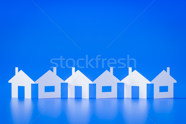 Stock photo: a paper cutout row of houses blue background