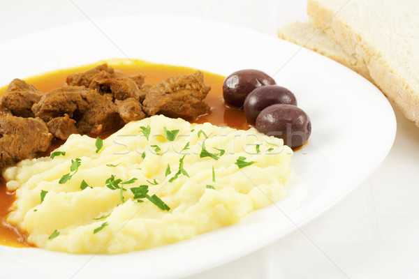 Goulash with potato puree, olives and bread Stock photo © magraphics