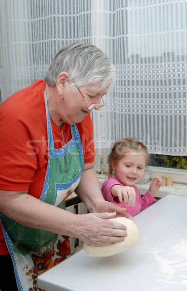 Grandmother and granddaughter knead the dough Stock photo © mahout