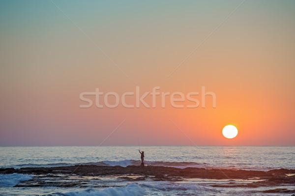 Silueta puesta de sol hombre peces sol mar Foto stock © mahout