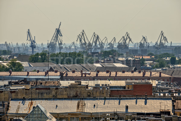 Old roofs in central part of St. Petersburg and port cranes Stock photo © mahout