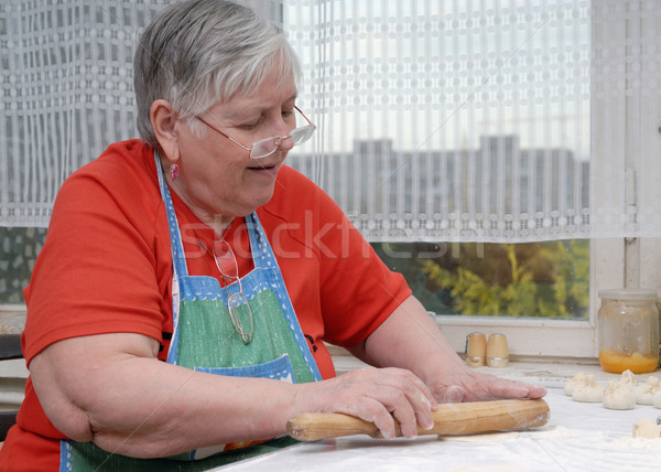 Elderly woman kneading dough Stock photo © mahout