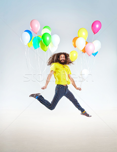 Conceptual portrait of a childish man jumping with balloons Stock photo © majdansky