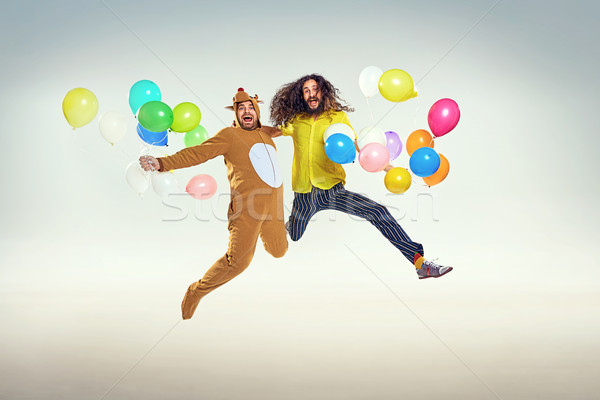 Picture presenting two funny guys jumping and holding balloons Stock photo © majdansky