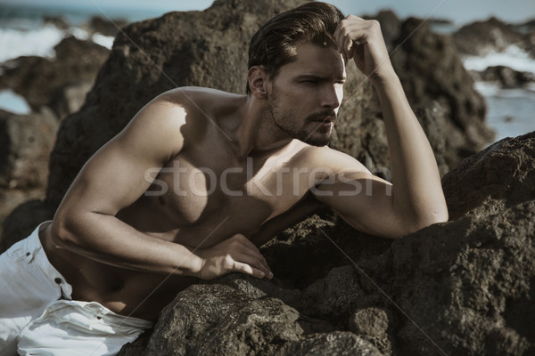 Musculaire Guy posant mer roches forte Photo stock © majdansky