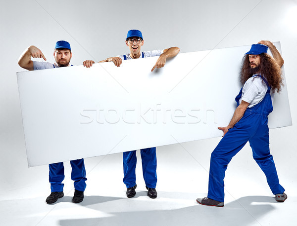 Conceptual picture of three crafstmen holding an empty board Stock photo © majdansky